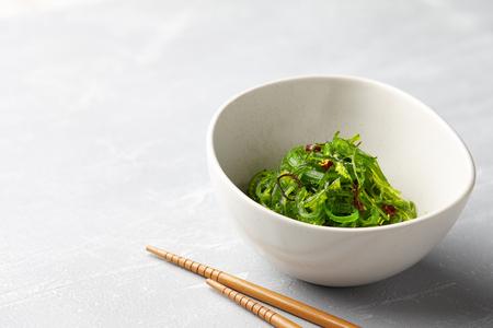Japanese chuka wakame salad with seaweed and sesame seeds on stone background