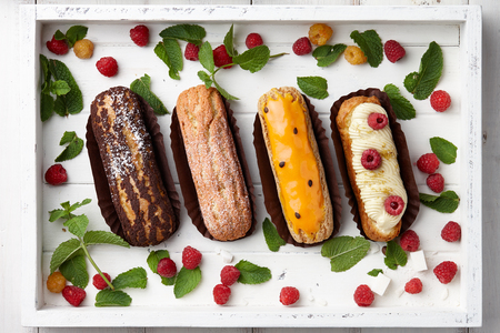 White wooden tray with french eclairs, raspberries and mint leaves, top view Stock Photo