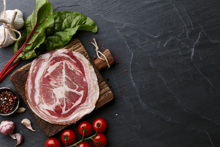 spice: Traditional Spanish smoked serrano ham or jamon on stone textured background, top view