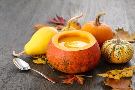 Fall pumpkin soup in big decorative pumpkin on dark wooden background Stock Photo