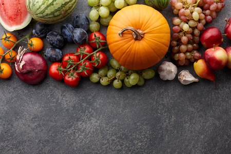 Autumn harvest concept. Seasonal fruits and vegetables on a stone tabletop, top view Stock Photo