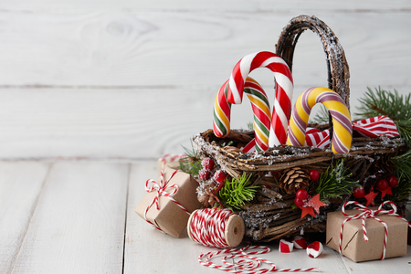 Christmas wicker basket with striped candy canes and gifts on white wooden table, festive decoration Stock Photo