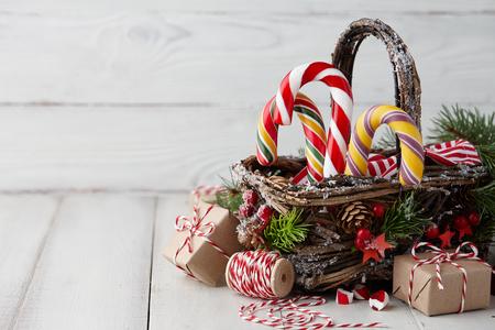 Kerstmis rieten mand met gestreepte suikergoedriet en giften op witte houten lijst, feestelijke decoratie Stockfoto