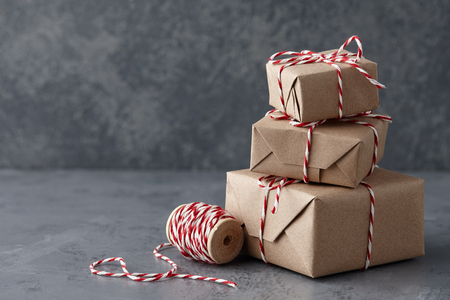 Christmas gift or present boxes wrapped in kraft paper with striped bakers twine string on textured stone background, copy space