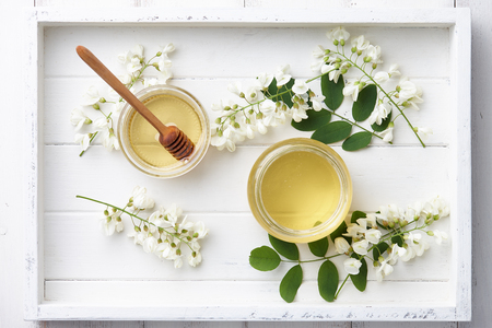 White wooden tray with sweet honey jar and spring acacia blossoms, top view Stock Photo