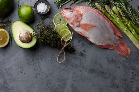 Raw red tilapia fish cooking with herbs, spices, green asparagus, avocado, lemon and lime on gray stone background, top view