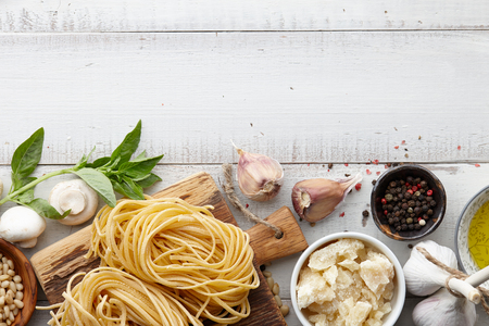 Raw homemade italian pasta and ingredients on white wooden background, cooking process Stock Photo