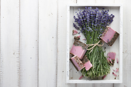 Lavender soap and beautiful lavender flowers in white box, top view