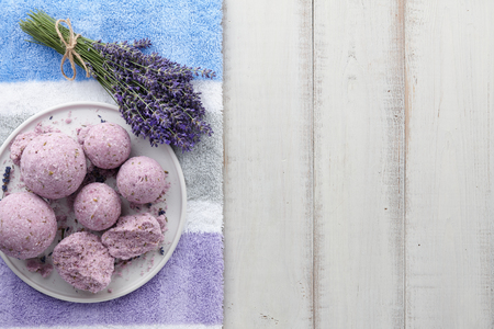 Natural cosmetics. Lavender bath bombs, flowers and towel on white wooden planks, top view
