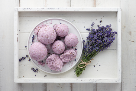 Handmade lavender bath bombs and lavender flowers in white wooden tray, top view