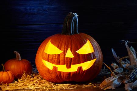 Carved pumpkin or so called jack-o-lantern in dark barn, Halloween holiday celebration concept