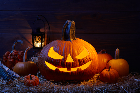 Carved pumpkins or so called jack-o-lanterns in dark barn, Halloween holiday celebration concept Imagens