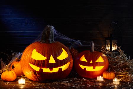 Carved pumpkins or jack-o-lanterns in dark barn, Halloween holiday celebration concept