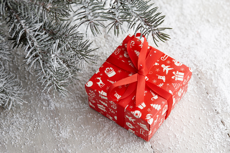 Christmas red gift box with festive pattern and ribbon under snowy fir tree