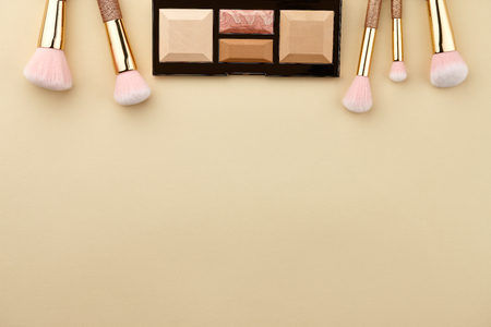 Make up palette and brushes on beige background, close up view