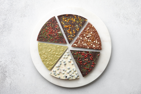 Round chocolate pizza pieces with diverse kinds of chocolate on stone tray on textured background, top view