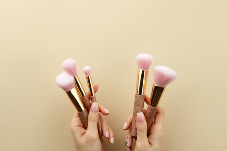 Womans hands holding golden glossy make up brushes with pink bristles on beige background, close up view, copy space