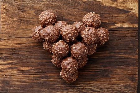 Heart shape made from chocolate truffle candies with hazelnuts on wooden background, top view 版權商用圖片