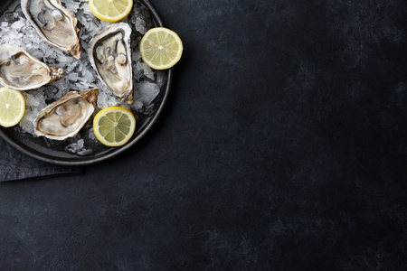 Fresh opened oysters in a plate with ice and lemon on black textured background, top view Stock Photo