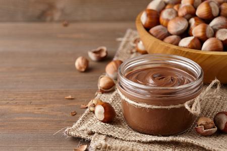 Crema spalmabile al cioccolato o torrone con nocciole in barattolo di vetro su fondo di legno, spazio copia