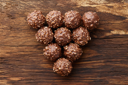 Chocolate truffle candies with hazelnuts shaped in triangle on wooden background, top view