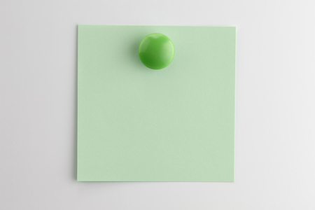 Square blank sheet of green paper pinned with a button magnet on white refrigerator