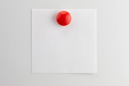 Square blank sheet of white paper pinned with a red button magnet on white refrigerator