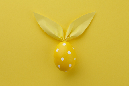 Yellow dotted Easter egg with paper bunny ears on lemon yellow background. Holiday concept. 免版税图像