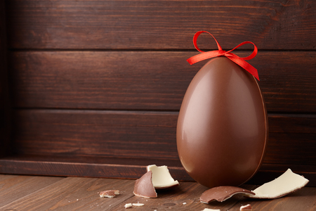 Chocolate Easter egg gift with red bow on dark wooden background, holiday concept Stockfoto