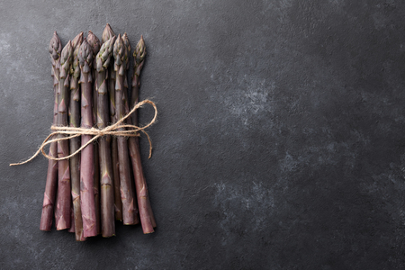 Bunch of fresh purple asparagus on black textured background, copy space