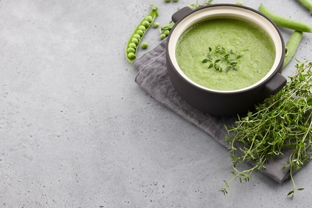Fresh green pea soup served in bowl with thyme on gray concrete background, copy space