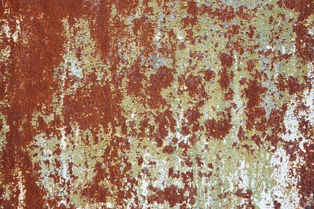 Vintage texture of old rusty metal sheet with cracking paint and chipping look. Antique background.