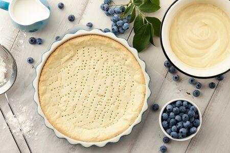 Pie crust, custard and fresh blueberries on white wooden planks. Cooking blueberry pie. Stockfoto
