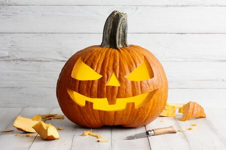 Carving Jack-o-Lantern from big pumpkin for Halloween celebration, holiday decoration