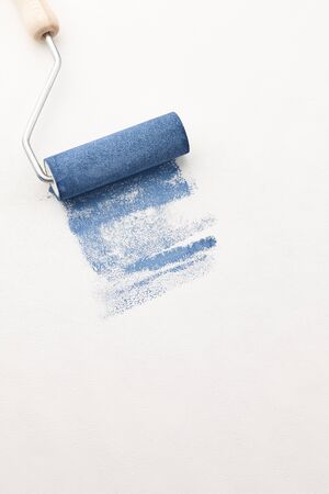Sponge roller with blue paint on white wallpaper background, copy space