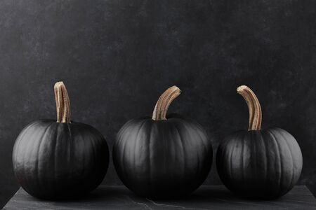 Black pumpkins on black textured background, Halloween decoration Stockfoto