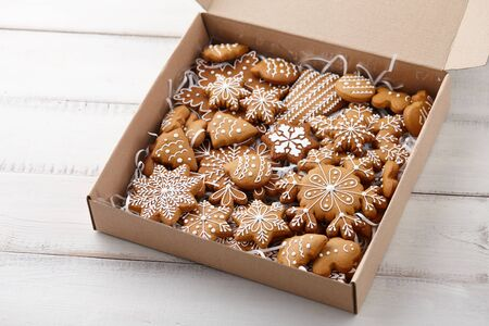 Christmas gingerbread cookies in cardboard box on white wooden background, holiday concept Banco de Imagens