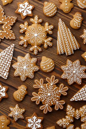 Christmas gingerbread cookies on brown wooden background, top view