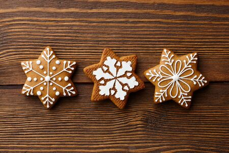 Christmas gingerbread snowflake cookies on brown wooden background, holiday concept Banco de Imagens