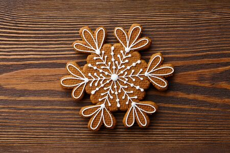 Christmas gingerbread snowflake cookie on brown wooden background, holiday concept