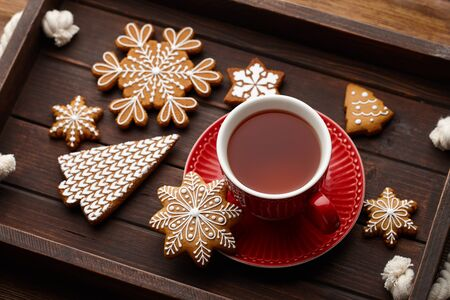 Winter cup of tea with Christmas gingerbread cookies on wooden background Banco de Imagens
