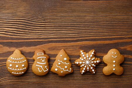 Christmas gingerbread cookies on brown wooden background, holiday concept Banco de Imagens