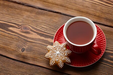 Winter cup of tea with Christmas gingerbread cookie on wooden background Stock Photo