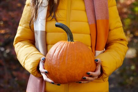 Woman in yellow casual jacket holding orange pumpkin on colorful fall leaves background, close up view