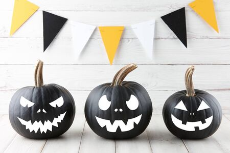 Halloween black pumpkins with scary faces on white wooden planks, holiday decoration Stock Photo