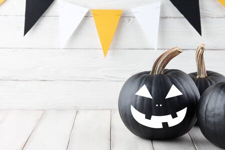 Halloween black pumpkins with scary faces on white wooden planks, holiday decoration Banco de Imagens