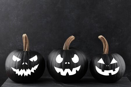 Halloween black pumpkins with scary faces on black background, holiday decoration