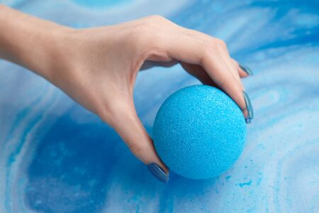 Woman's hand putting blue bath bomb into water, copy space