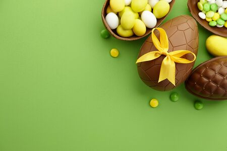 Chocolate Easter eggs and colorful candies on green background, copy space Standard-Bild - 143527213
