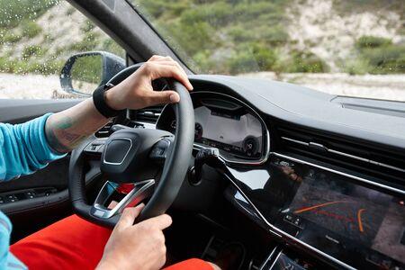 Man driving car cross country in Alps, summer traveling Foto de archivo